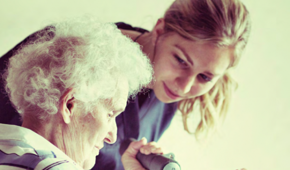 young lady helping elderly lady with soft weight exercise
