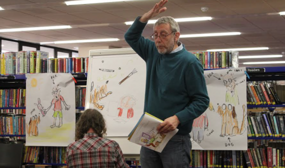 Teacher demonstrating in front of a class in a library
