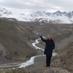 Woman stands in front of stream with mountains in the background