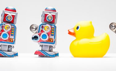 a line of toy robots with one rubber duck in the middle
