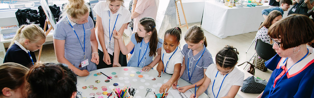 Children crowded around a table designing badges