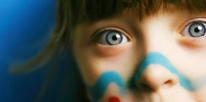 close up of girl with blue eyes and face paint