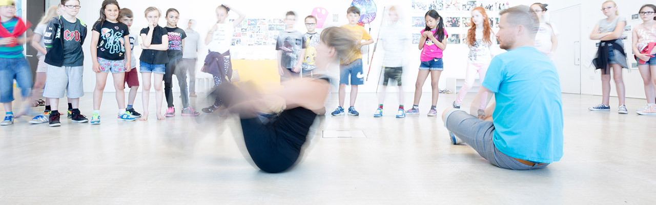 Dance teacher spinning on the floor as a crowd of children look on