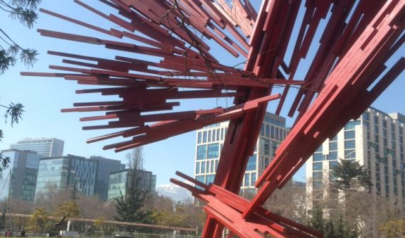 red abstract modernistic statue in park