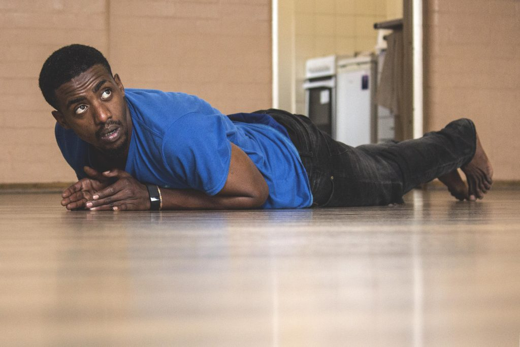 Male student laying on studio floor in performance