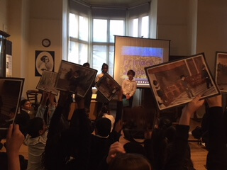 Young people in front of a projector screen with a crowd of children holding up pictures