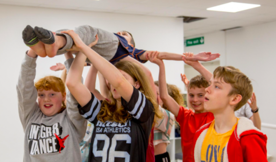 Group of young people lift a boy making a cross shape with his arms over their heads