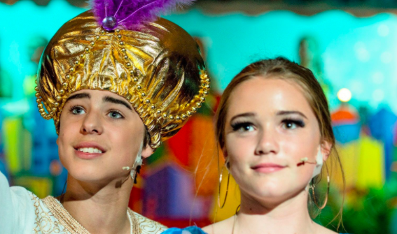 Close up of two performers in costume and wearing microphones during school production