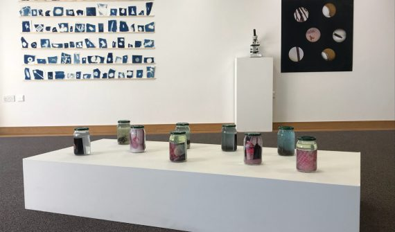 Gallery display of art work produced during the programme including cyanotypes shown on the wall in rows, coloured jars containing marine plants and pollutants and a magnifying glass next to an enlarged image of things found under the microscope.