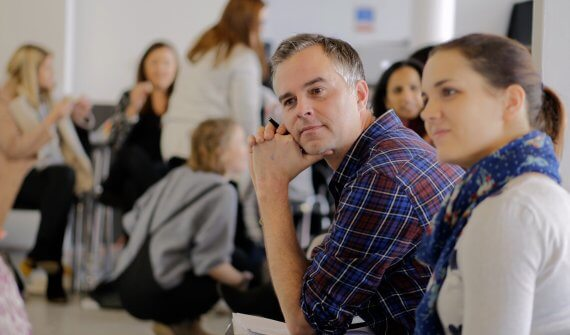Male teacher looks and listens to a group discussion