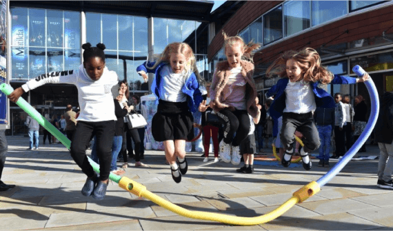 Four primary school aged girls jump over a large skipping rope made of three coloured foam noodles