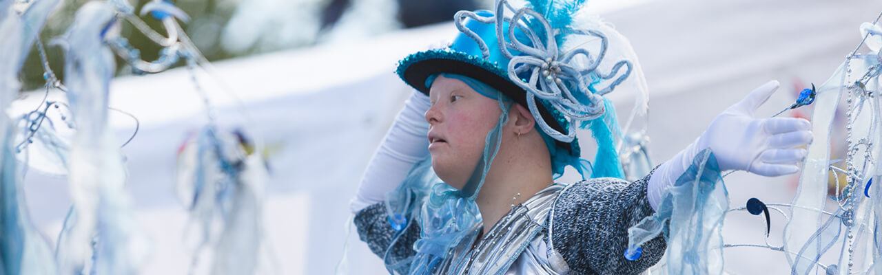 Young person in blue and silver costume waving whilst performing in the Mardi Gras parade