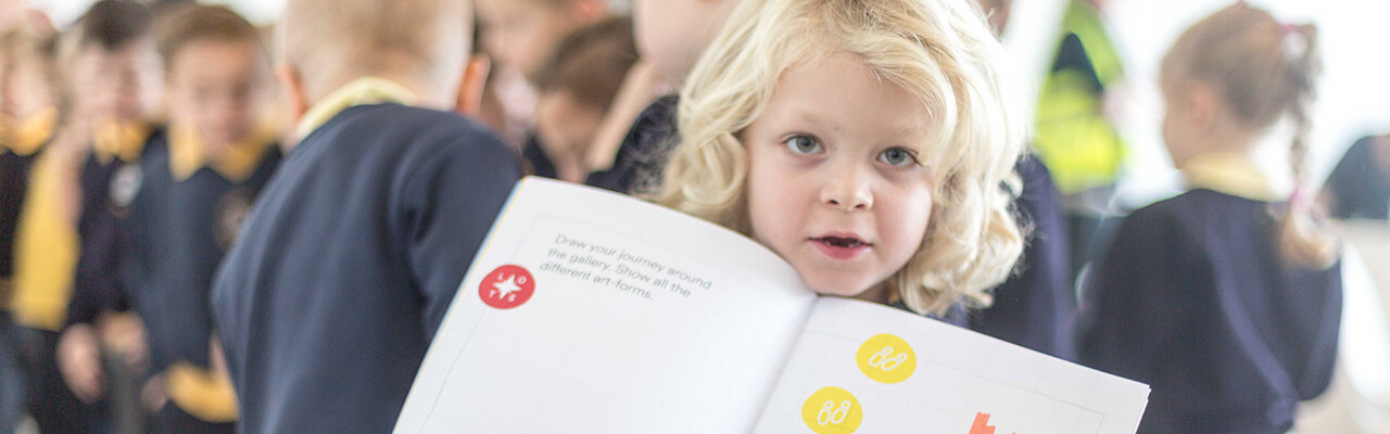 Young child holding workbook open to show their work to the camera