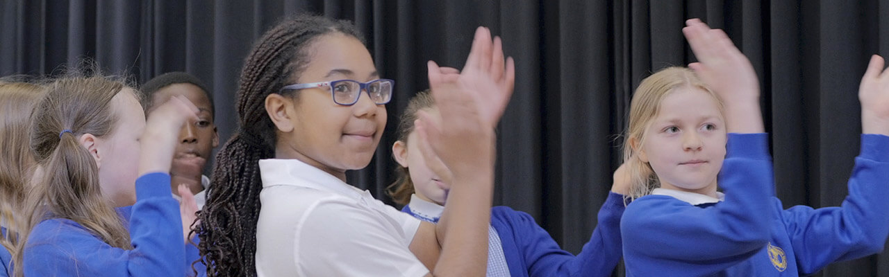School children clapping along as they practice some dance choreography