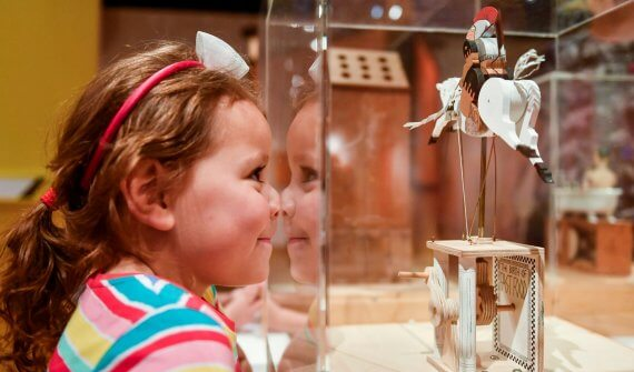 Little girl pushing her nose up against the glass case around a horse automata