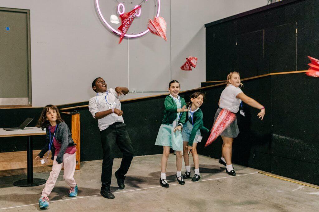 Schoolchildren racing paper aeroplanes in a line