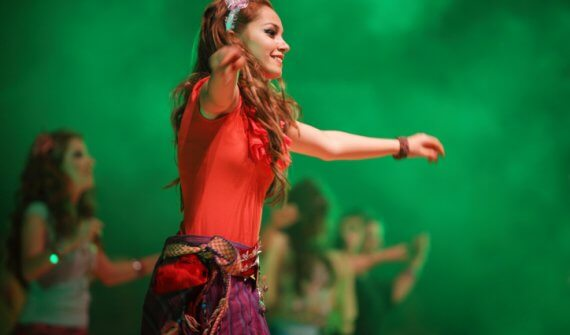 Image of young performer surrounded by green fog, dressed in a homemade costume