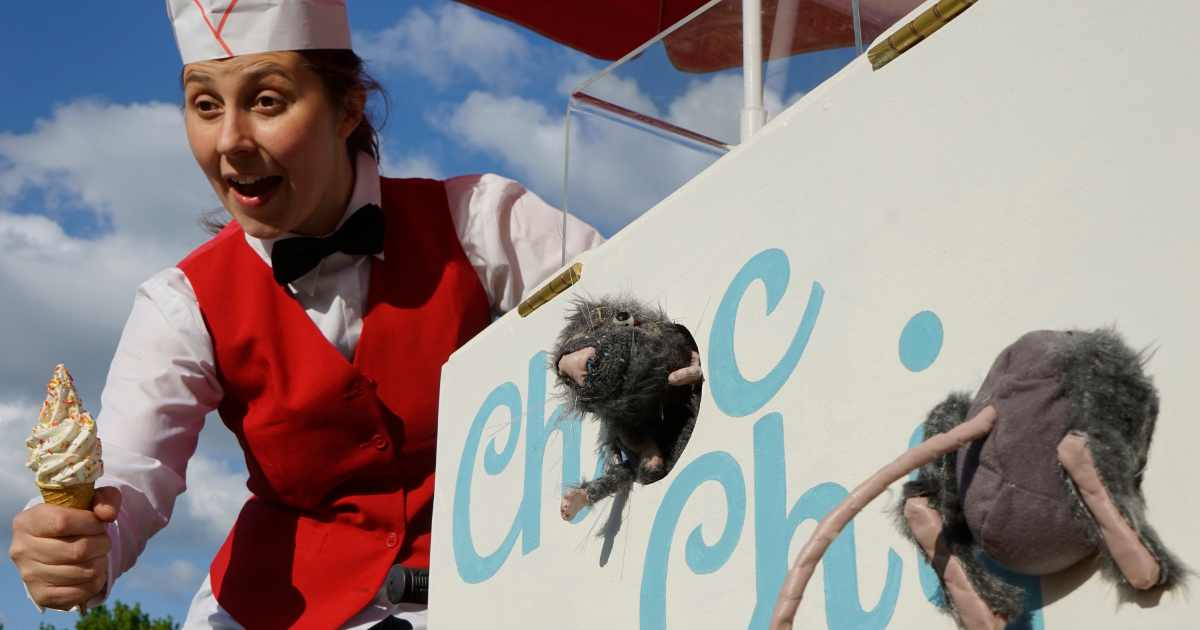 Woman dressed in ice cream parlour uniform next to sign that says 'choc chip' which has puppet rats poking out of it