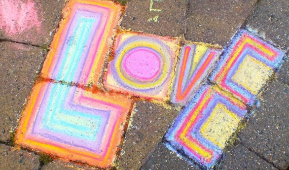 The word 'LOVE' written in multicoloured chalk on pavement