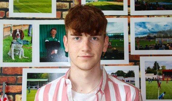 Image of Harry head and shoulders view wearing a pink and white stripe shirt stood in front of a display of his photography work