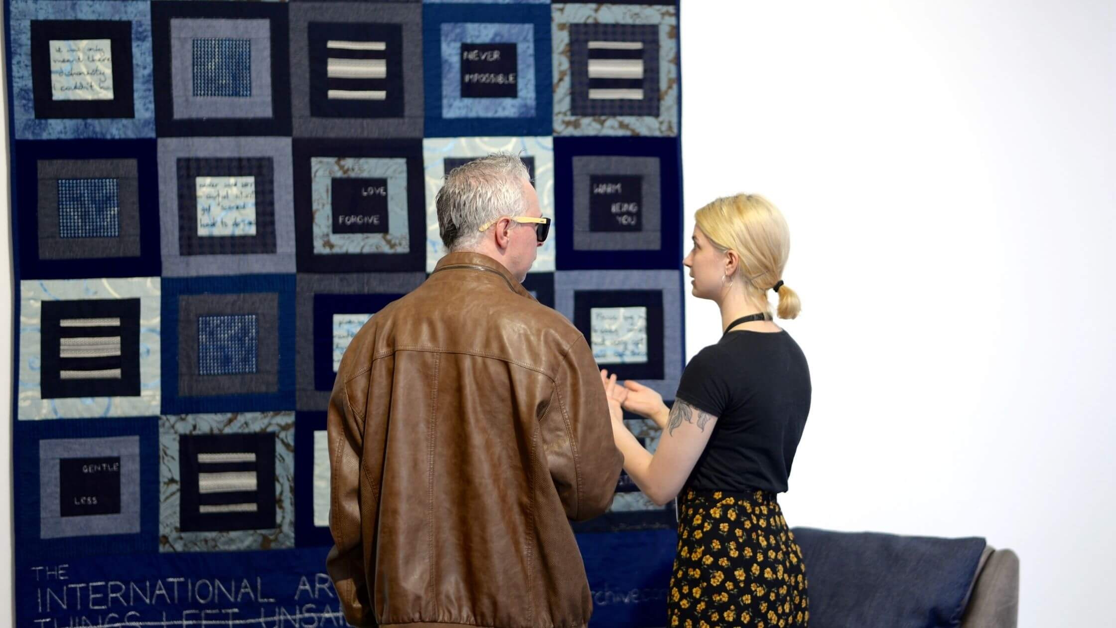 Image of Harriet talking to a man as they admire a patchwork quilted piece of art hung on a gallery wall.