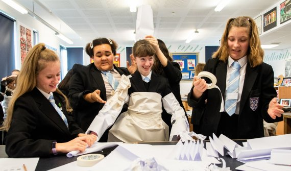 Group of secondary school age children creating a costume out of white paper and dressing up the young person in the middle