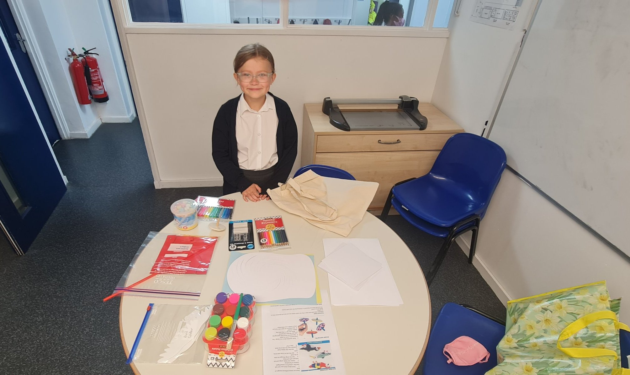 Smiling child stood behind a school desk covered in art and craft supplies including paint and colouring pencils