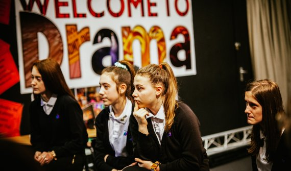 Group of four secondary school-aged children sat listening attentively in a drama studio with a poster on the wall behind that reads 'Welcome to Drama'.