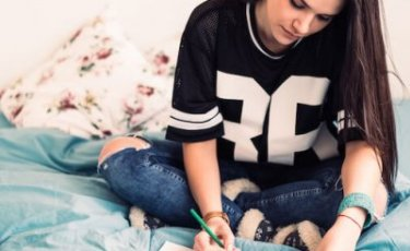 Young woman is sitting on her bed drawing with bright pencils.